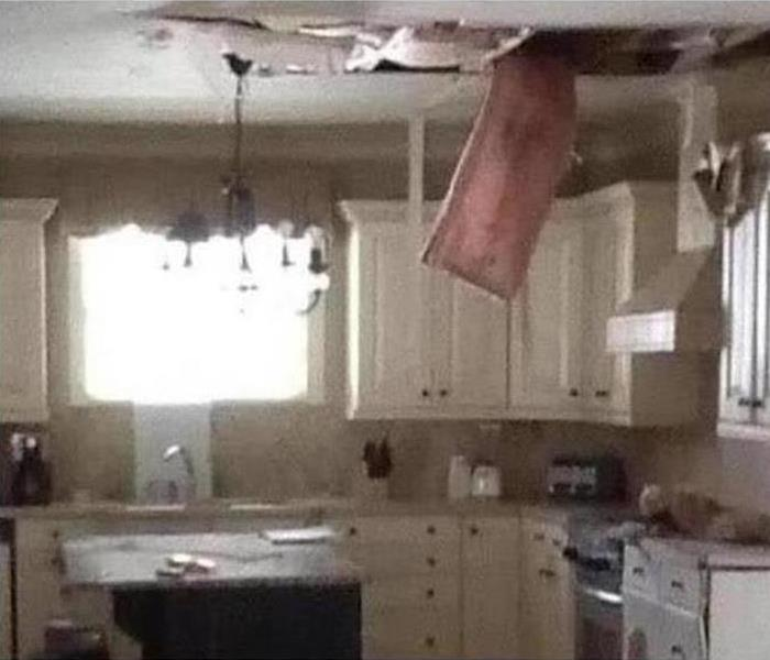 Kitchen with ceiling damage caused by storm.